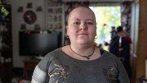 Porträttbild av Anja Viljanen stående i sitt vardagsrum.