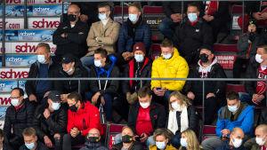 Publik under ishockeymatch bär ansiktsskydd.