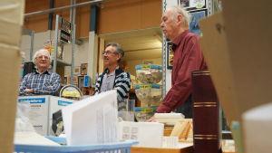 Tre män står och talar i en affär.