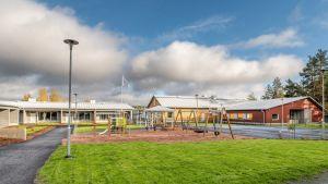 Innergården till Lauste familjerehabiliteringscenter, med en grön gräsmatta, gungor och en lekplats ingärdade av radhus.