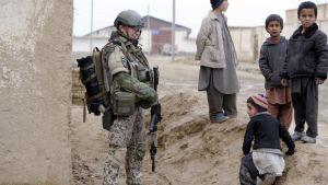 En finländsk soldat står och ser på lekande barn