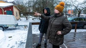 Kikke Heikkinen och Birgitta Montulet ser ut över en gårdsplan i snö.