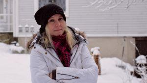 En kvinna med blont hår står utomhus i mössa och vinterkläder. Det är snö på marken.
