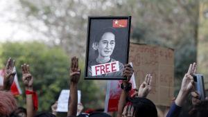 Demonstranter håller tre fingrar i luften och bär på ett porträtt av den fängslade regeringschefen Aung San Suu Kyi.