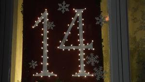 Snöflingor klippta i papper i ett fönster med numret 14.