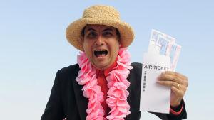 en medelålders kostymklädd man står på en strand med solhatt på och en flygbiljett i handen. Han ler ivrigt in i kameran.