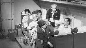 """""""Iskelmäkaruselli esittää turismi-iskelmiä"""".  Esiintyjiä lentokoneen matkustamoa esittävässä lavasteessa. Takaa vasemmalta Ritva Kinnunen, tunnistamaton naisesiintyjä, Brita Koivunen, Eino Virtanen, Paavo Einiö ja Reino Helismaa."""