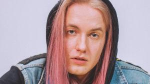 Nuori mies vaalenpunaisissa, pitkähköissä hiuksissa katsoo välinpitämätön, vähän haastava ilme kasvoillaan kameraan. Päällään hänellä on täynnä bändien kangasmerkkejä oleva farkkuliivi, musta huppari ja neonkeltaiset tuulihousut.