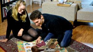 Petronella Nordman och Markus Bergfors sitter på golvet och läser för sin två månader gamla son Roy som ligger på en filt.