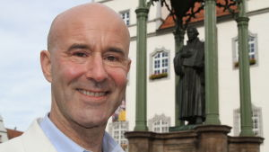 Mark Levengood i vit kavaj poserar på torget i Wittenberg, med staty i Martin Luther i bakgrunden