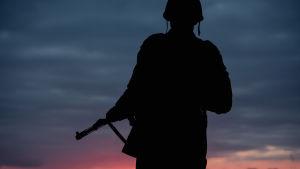 Siluetten av en soldat mot kvällshimlen.