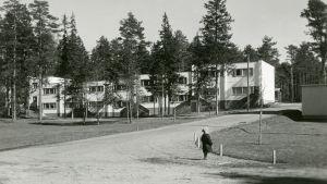 Liten pojke står på en sandväg, i bakgrunden ett nybyggt vitt tvåvåningsradhus. Bilden är svartvit och tagen på 1950-talet.