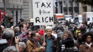 Demonstrant håller upp skyllt som kräver högre skatter för de rika i USA.