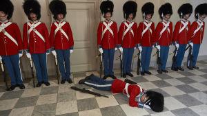 Avsvimmad danskl kunglig vakt på golvet medan de andra står i givakt.