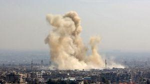 En bild tagen från regeringskontrollerat område i nordöstra Damaskus onsdagen 21.2. visar anfall mot Arbin och Harasta i östra Ghouta.