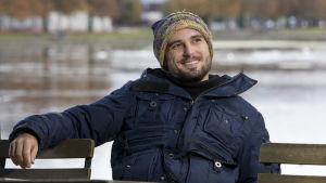 Christian Tafdrup sitter på en bänk och ler.