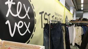 Kläder hänger på en klädstång i återvinningscentral.