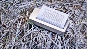Bild på dokumentförstörare i en hög med strimlade pappersbitar