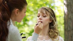 En kvinna sminkar en annan kvinna som är iklädd en vit spetsklänning. De befinner sig ute i skogen och solen skiner.