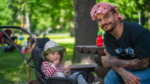 Wille Mäkelä sitter på en bänk och visar tummen upp. Hans dotter Ansa sitter i en barnvagn bredvid och äter en riskaka, med fundersam min.