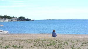 Kvinna med ryggen mot kameran sitter på en sandstrand och ser ut över havet en varm sommardag.