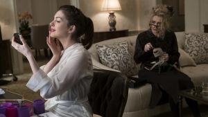 Daphne (Anne Hathaway) sitter vid ett bord och beundrar sin spegelbild, Rose Weil (Helena Bonham Carter) sitter i en soffa längre bort och ser på.