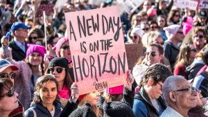 """Demonstration i San Francisco för kvinnors rättigheter, en kvinna håller upp ett plakat med texten """"a new day is on the horizon""""."""