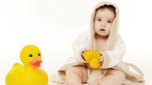 En babys i badkappa med en gul badanka i handen.