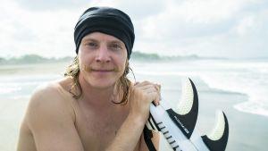 Kuvassa Away - Bali -sarjan Jeppe poseeraa surffilaudan kanssa.