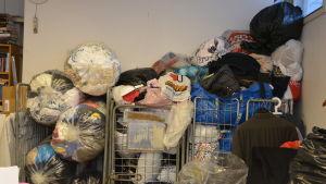 Återanvända kläder i en massa påsar på Emmaus-Westervik som ska sorteras.