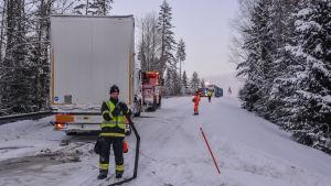 Brandman samlar upp slang medan bärgningsbilen drar iväg olyckslångtradaren