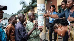 Väljare får sina handlingar kontrollerade utanför en vallokal i Port Harcourt, i södra Nigeria.