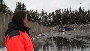 Cati Huhta tittar på traktorer som kör ihop avfall på Toppå sopstation