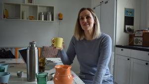 Kvinna med ljust hår och ljusblå klänning sittr vid ett vitt matbord och ler. I handen har hon en kaffemugg.