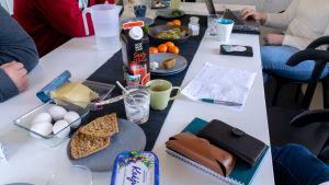 Ett bord fullt med papper och mat.