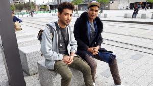 Två unga män sitter på en betonggris.