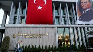 En bild på människor som går förbi ett hus. Turkiet flagga hänger på huset.