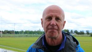 En skallig medelålders man står framför en fotbollsplan.