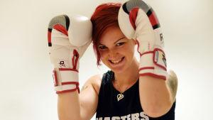 En bild på en kvinna (Emmy Erroll) med rött kort hår med boxningshandskar.