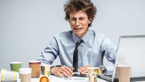 Mies itkee työpöytänsä ääressä.