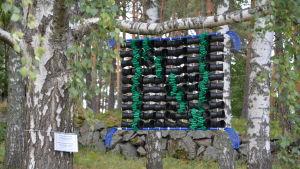 En blå innebandyklubba, svarta blomkrukor och gröna plastremsor bildar ett konstverk. Bokstaven N.