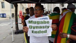 Zimababwier utanför Zimbabwes ambassad i London uttrycker sin glädje år 2017 över att Mugabe avsatts.