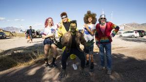 Fem personer utklädda till rymdvarelser poserar i närheten av Area 51.