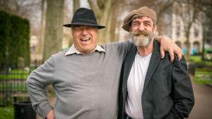 Glada äldre män i hattar håller om varandra i park