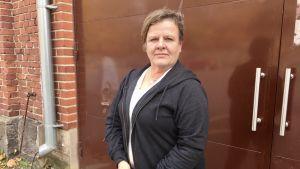 Ansa Holm står vid en metalldörr utomhus.