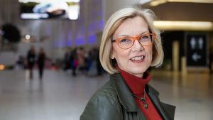 Saara Hassinen, terveysteknologian ry.:n toimitusjohtaja seisoo Helsingin messukeskuksen aulassa ja hymyilee..