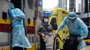 Sjukvårdare på gatan i blåa plastdräkter framför en ambulans. Bredvid står en kvinna och ett barn med ansiktsmasker.