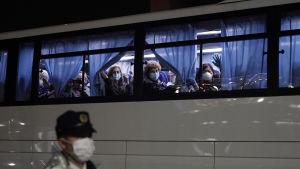 Amerikanska medborgare sitter i en buss och tittar ut ut fönstret. Bussen har blå gardiner som passagerarna håller i. Utanför bussen syns en person med ett andningsskydd och vit rock.