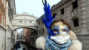 Ett barn iklätt ansiktsmask med en stor blå fjäder och andningsskydd vid en av Venedigs broar över kanalen.