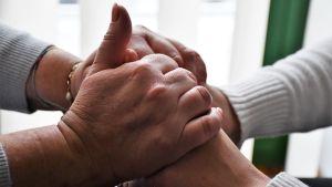 Två par händer håller om varandra.